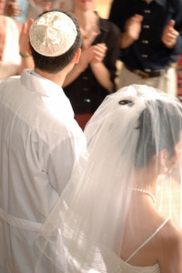 Jewish couple leaving their wedding ceremony.